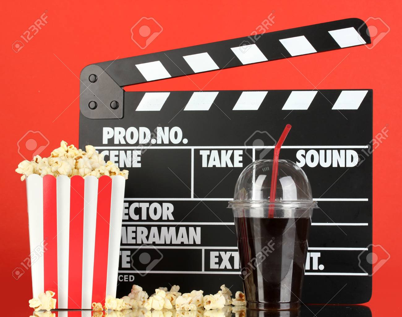 Movie clapperboard, cola and popcorn on red background Stock Photo - 16911299
