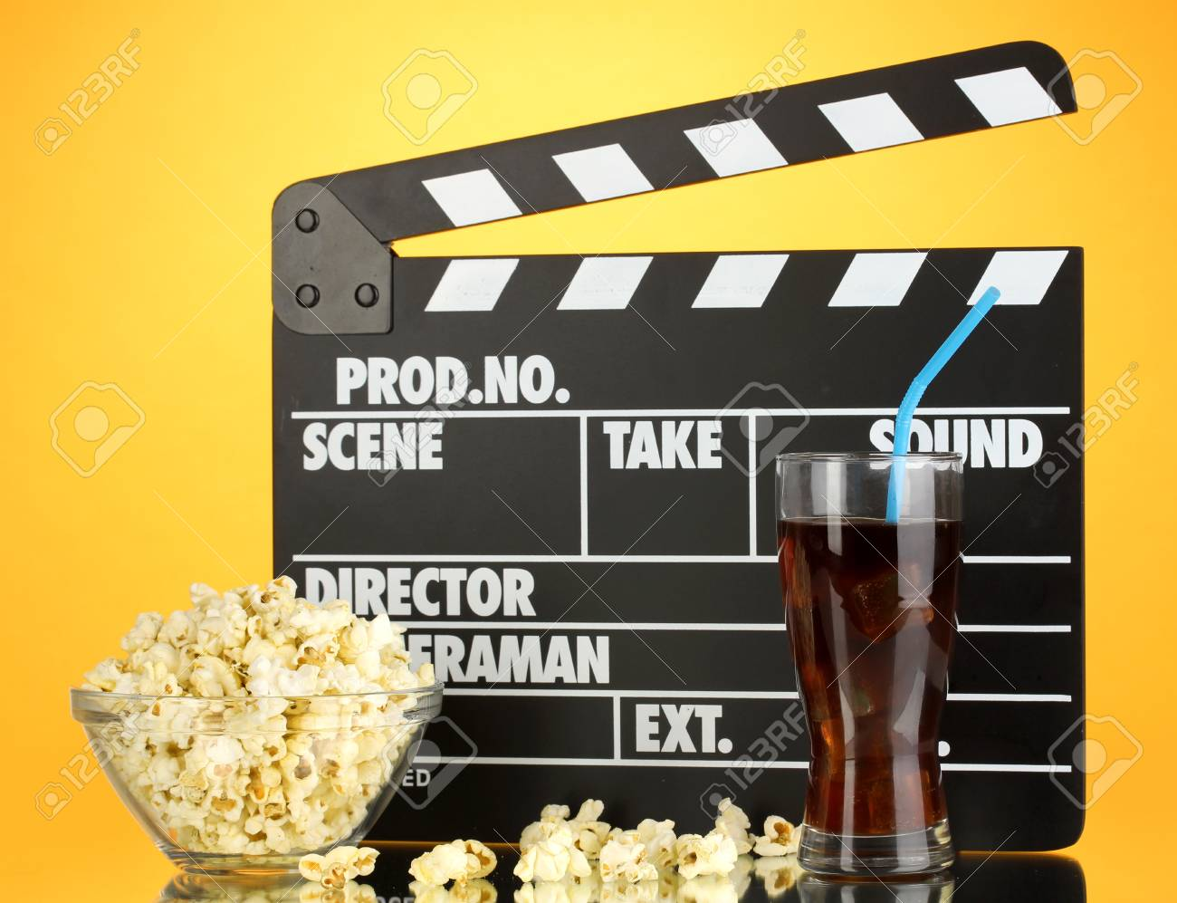 Movie clapperboard, cola and popcorn on orange background Stock Photo - 16998934