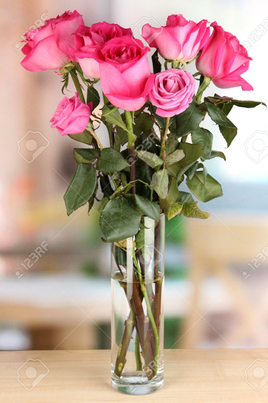 123RF.com & Beautiful pink roses in vase on table on room background