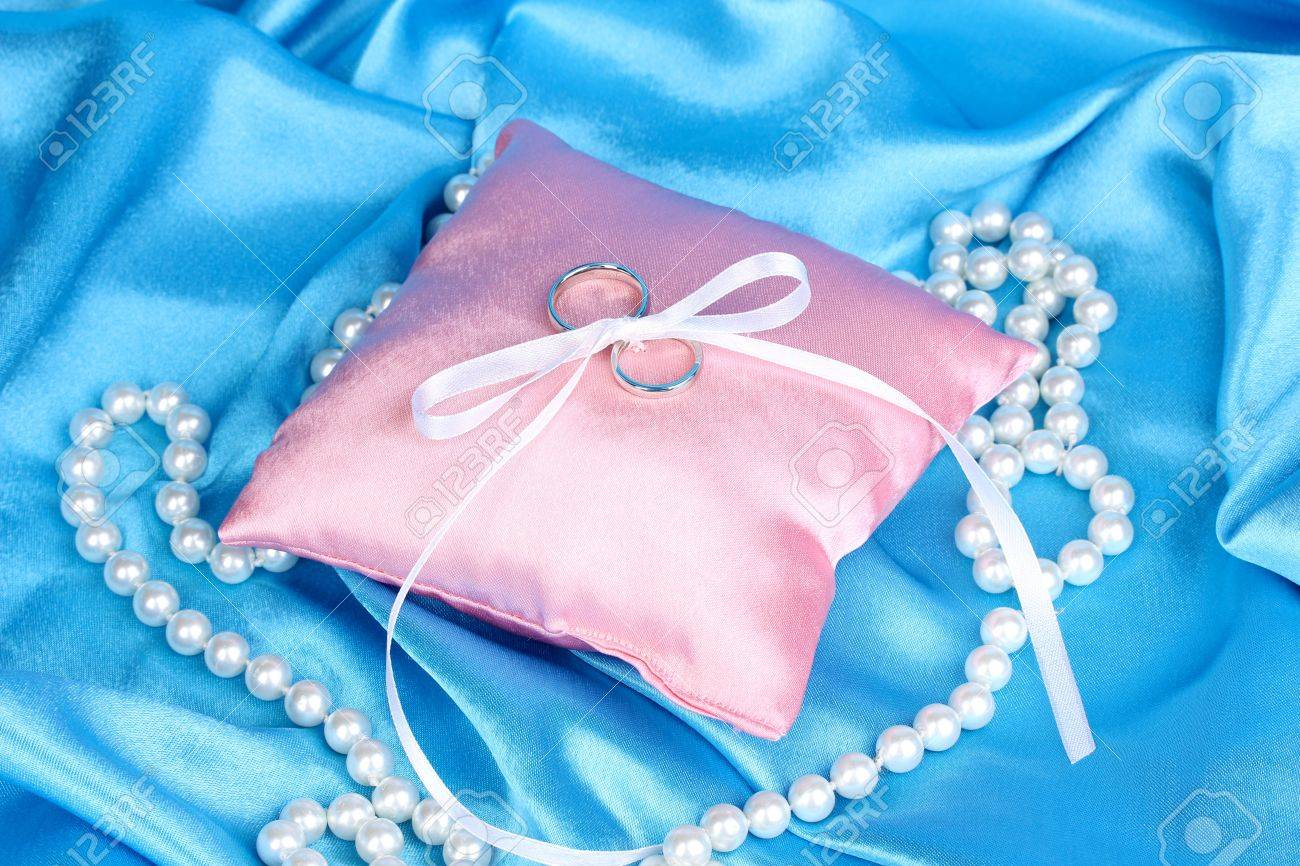 Wedding Rings On Satin Pillow On Blue Cloth Background Stock Photo ...