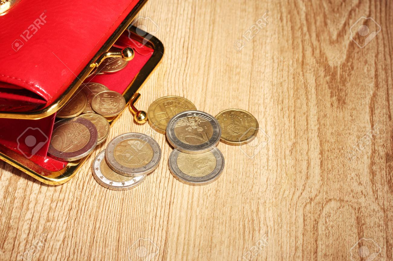 female red wallet with coins on wooden background Stock Photo - 17064370