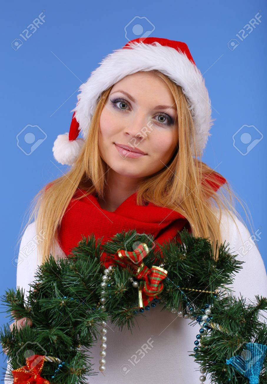 Attractive young woman holding Christmas wreath,on blue background Stock Photo - 17281540