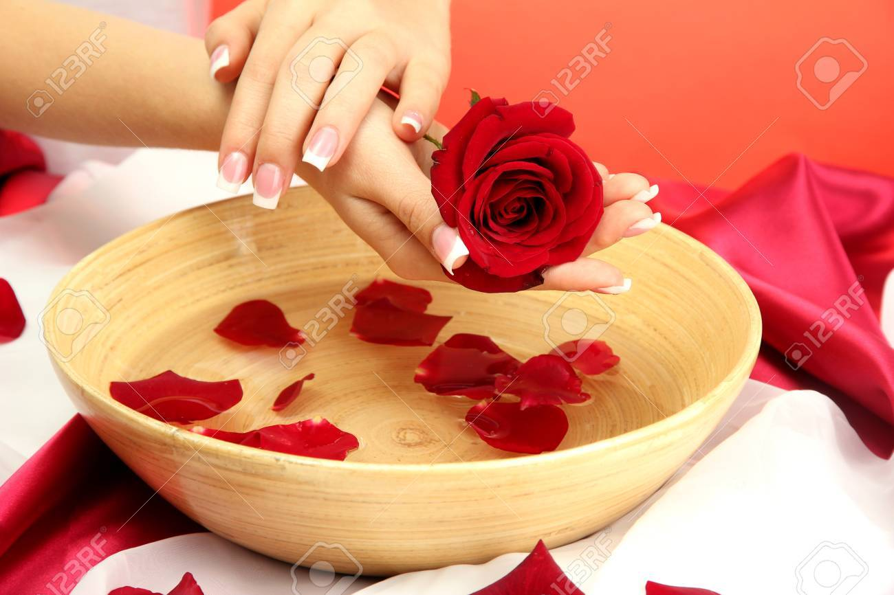 woman hands with wooden bowl of water with petals, on red background Stock Photo - 17143180