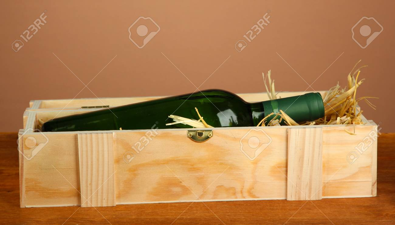 Wine bottle in wooden box on wooden table on brown background Stock Photo - 17143167