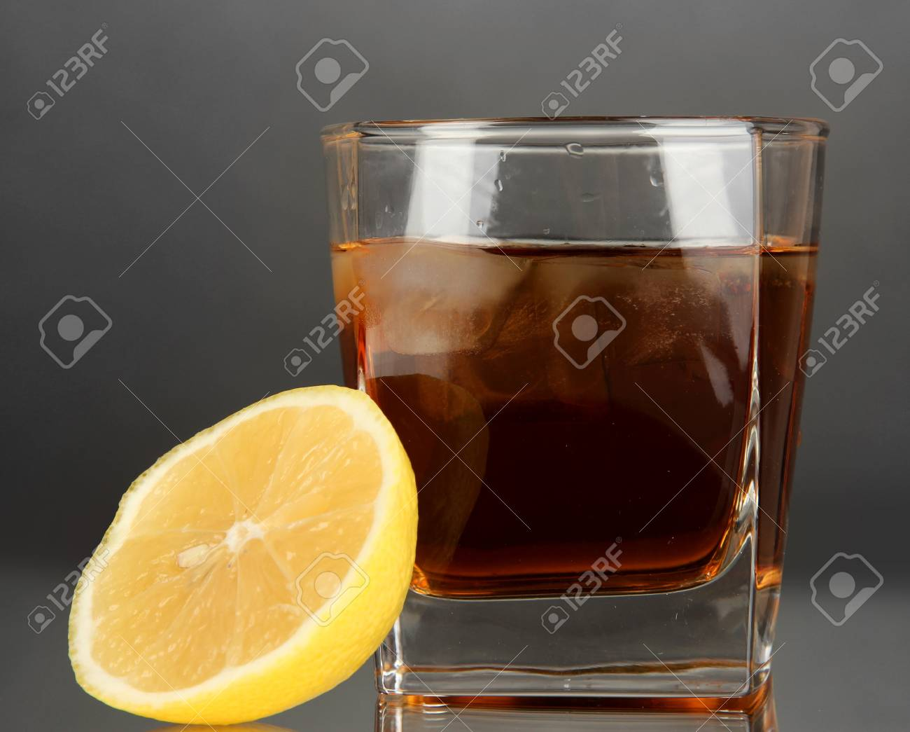Glass of whiskey with ice and lemon on grey background Stock Photo - 17140742