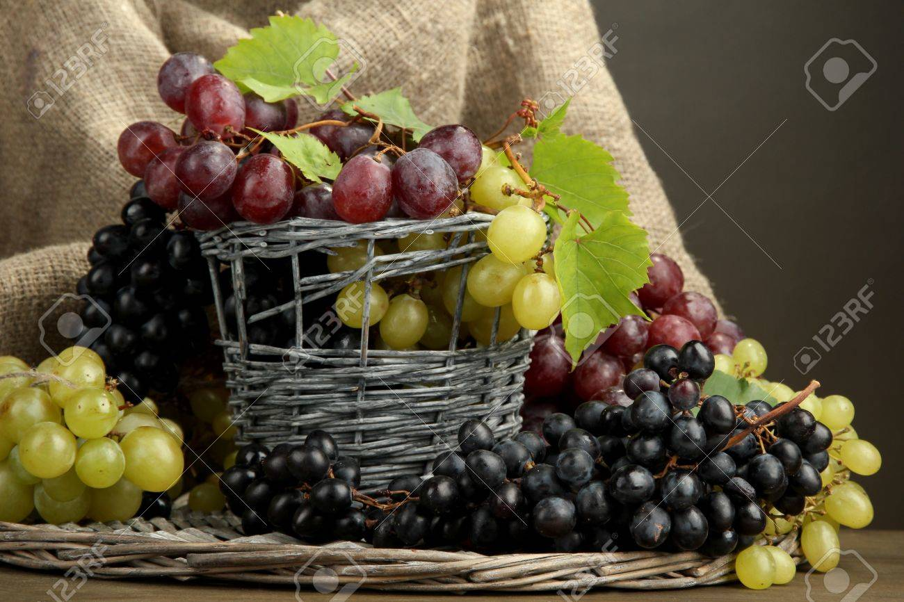 assortment of ripe sweet grapes in basket, on grey background Stock Photo - 17292294
