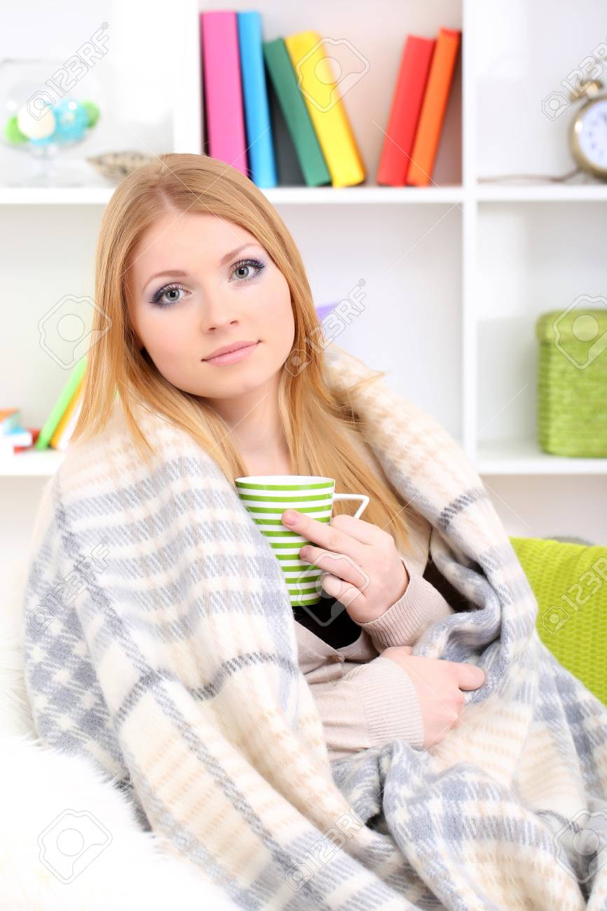 Attractive young woman sitting on sofa, holding cup with hot drink, on home interior background Stock Photo - 17544495