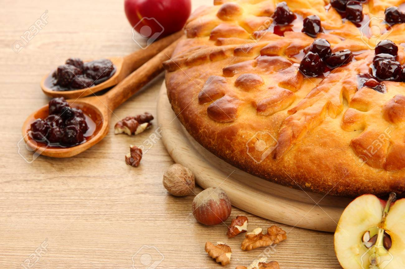 tasty homemade pie with jam and apples, on wooden table Stock Photo - 17467094