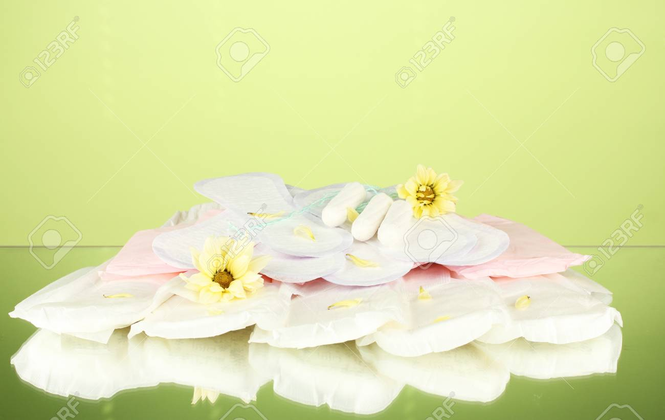 various types of sanitary pads and tampons on green background close-up Stock Photo - 17517027