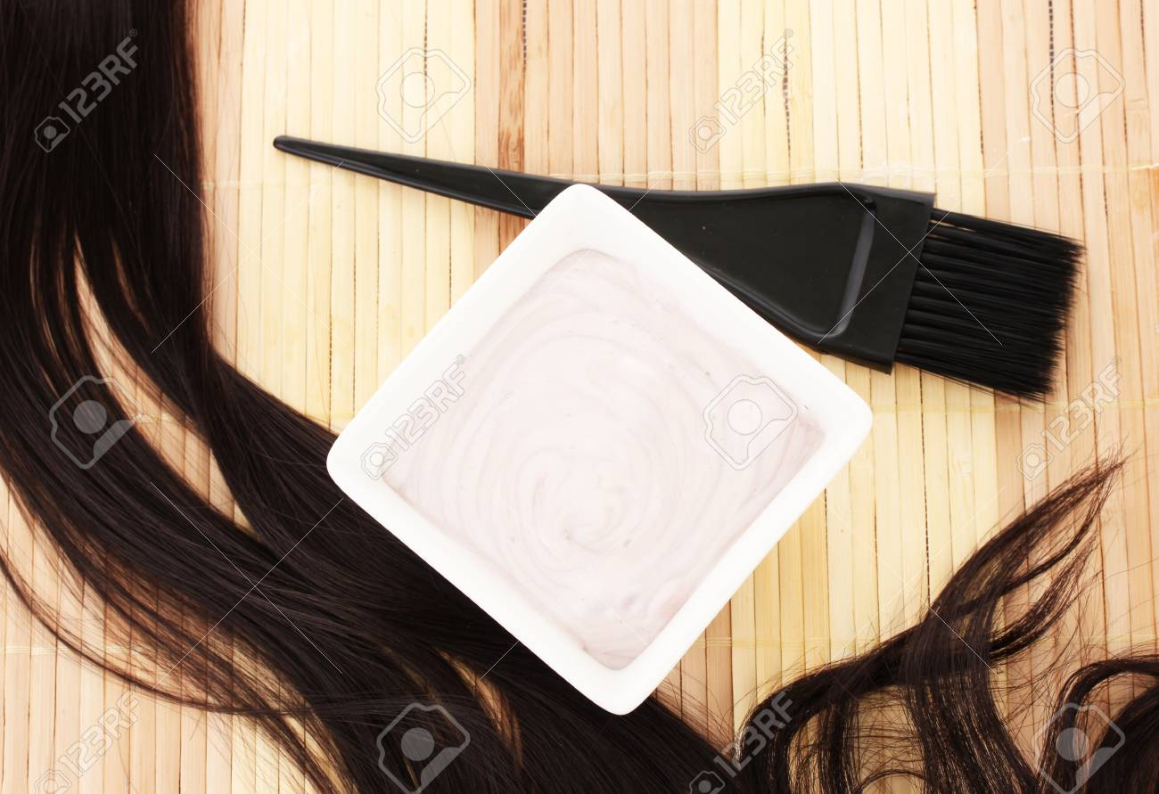 Hair Dye In Bowl And Brush For Hair Coloring On Beige Bamboo Stock