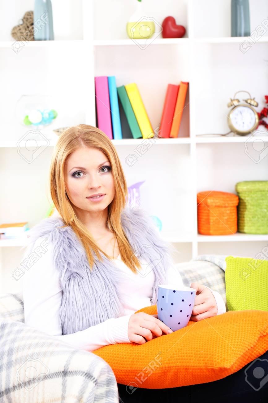 Attractive young woman sitting on sofa, holding cup with hot drink, on home interior background Stock Photo - 17761976