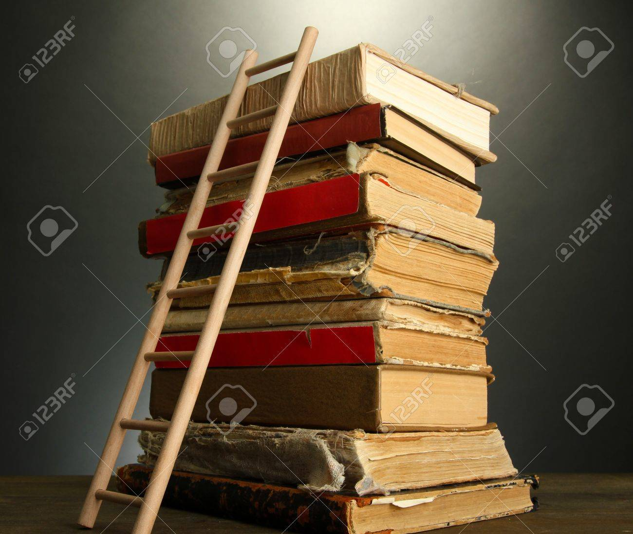 Old books and wooden ladder, on grey background Stock Photo - 17864196