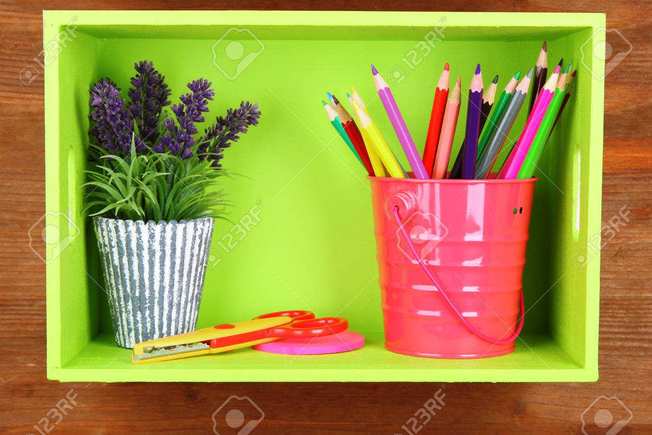 Colorful pencils in pail on shelf on wooden background Stock Photo - 18316732