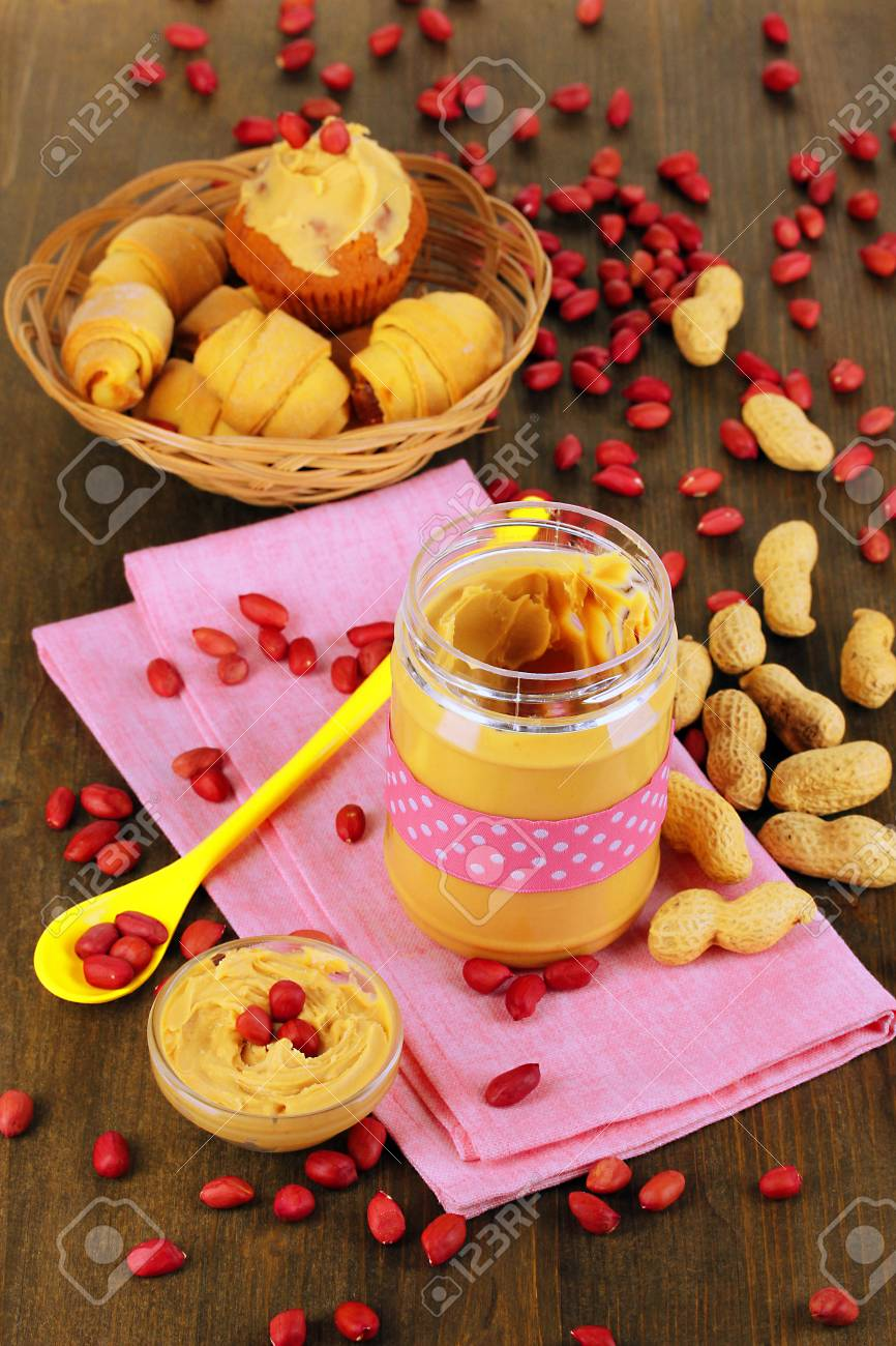 Delicious peanut butter in jar with baking on napkin on wooden table close-up Stock Photo - 18472995