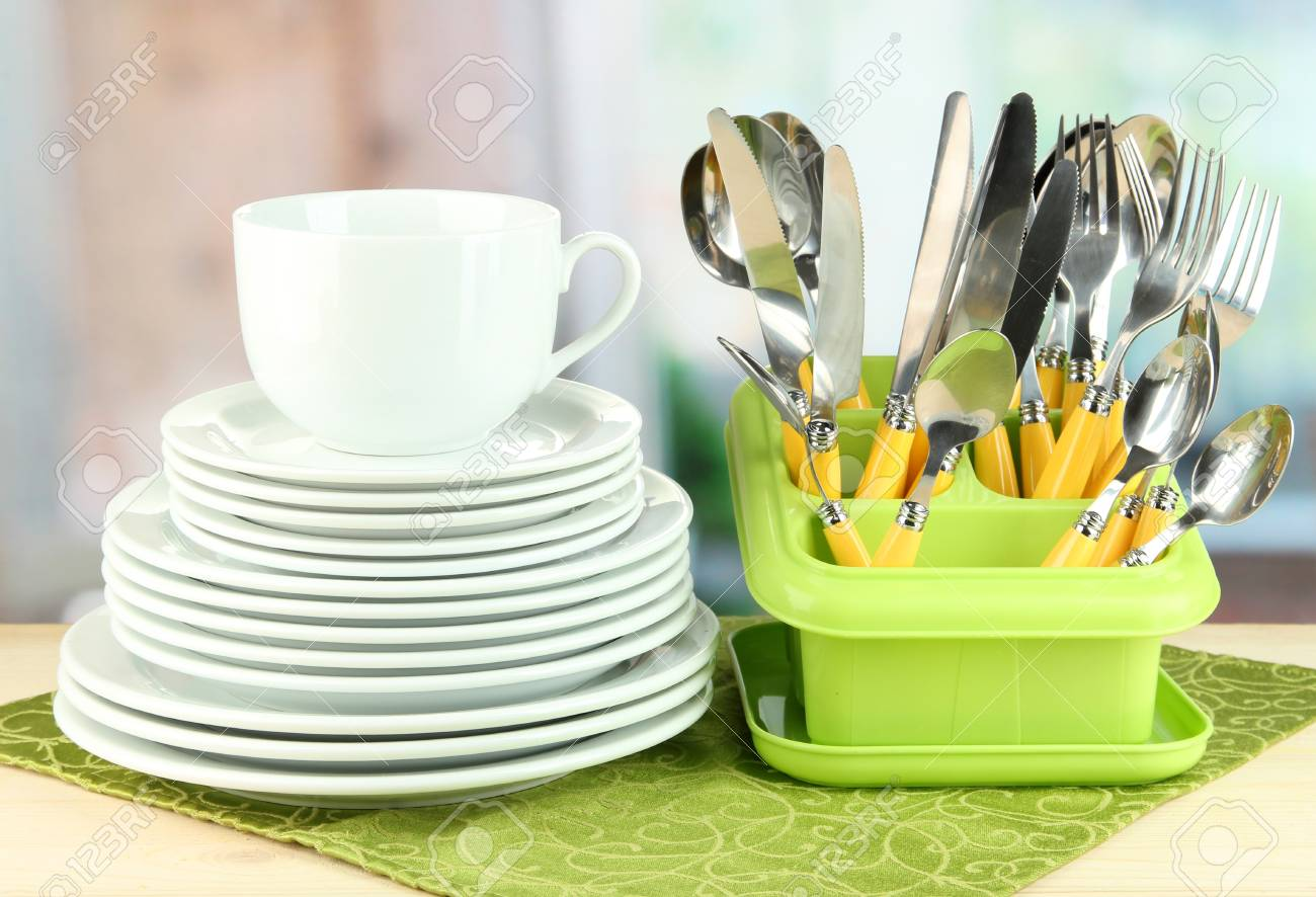 Plates, forks, knives, spoons and other kitchen utensil on color napkin, on