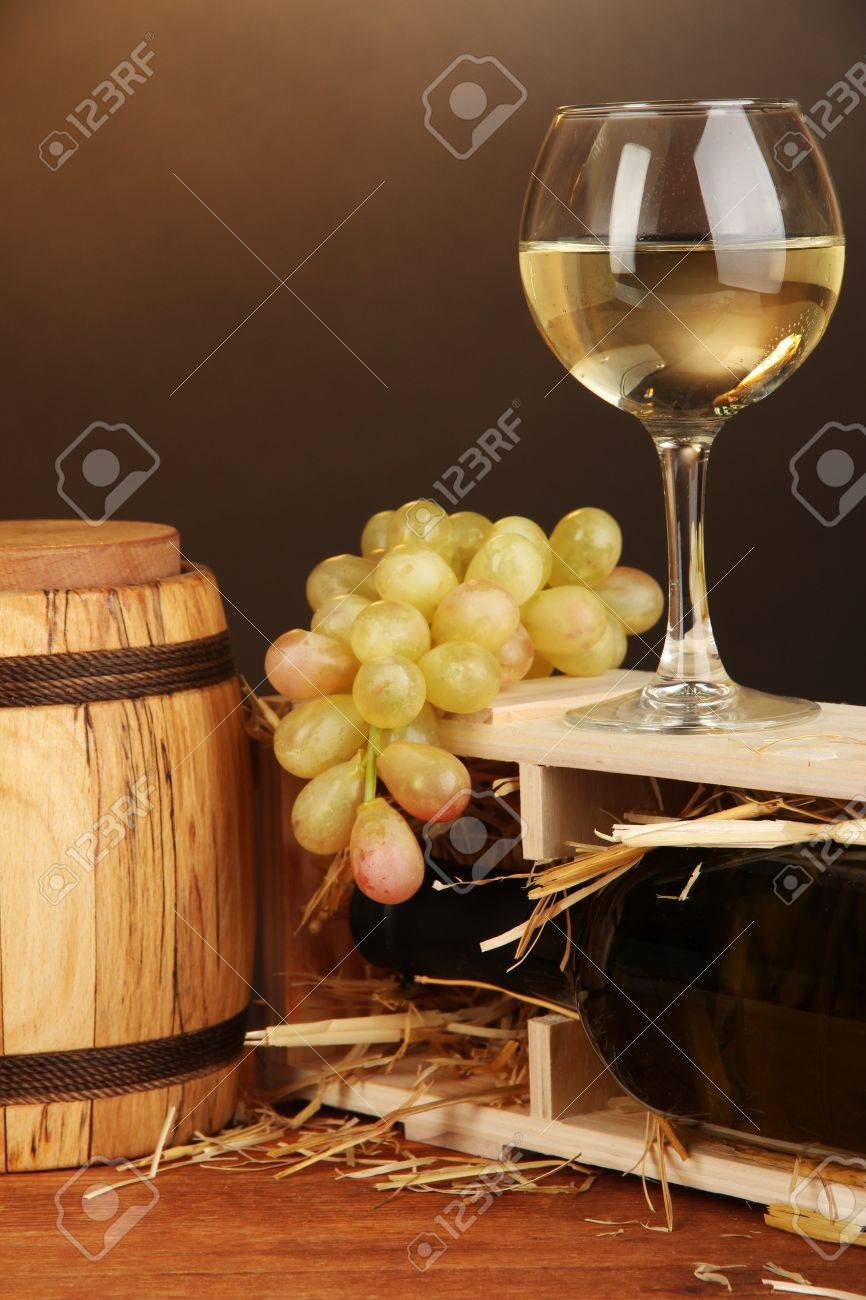 Wooden case with wine bottle, barrel, wineglass and grape on wooden table on brown background Stock Photo - 18695401