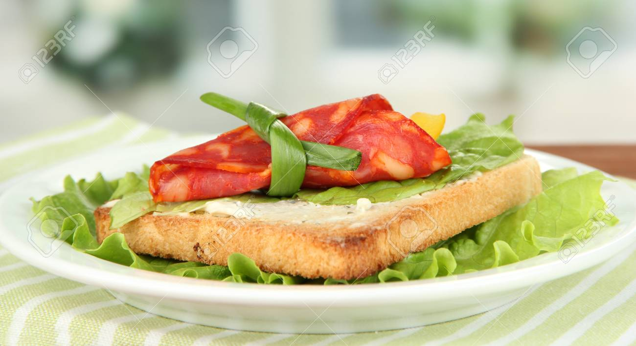 Salami rolls with paprika pieces inside, on  roasted bread with cheese cream, on bright background Stock Photo - 18716339