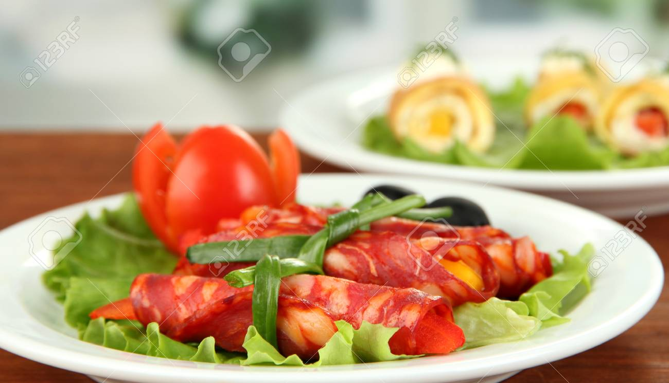 Salami rolls on white plate on bright background Stock Photo - 18800663