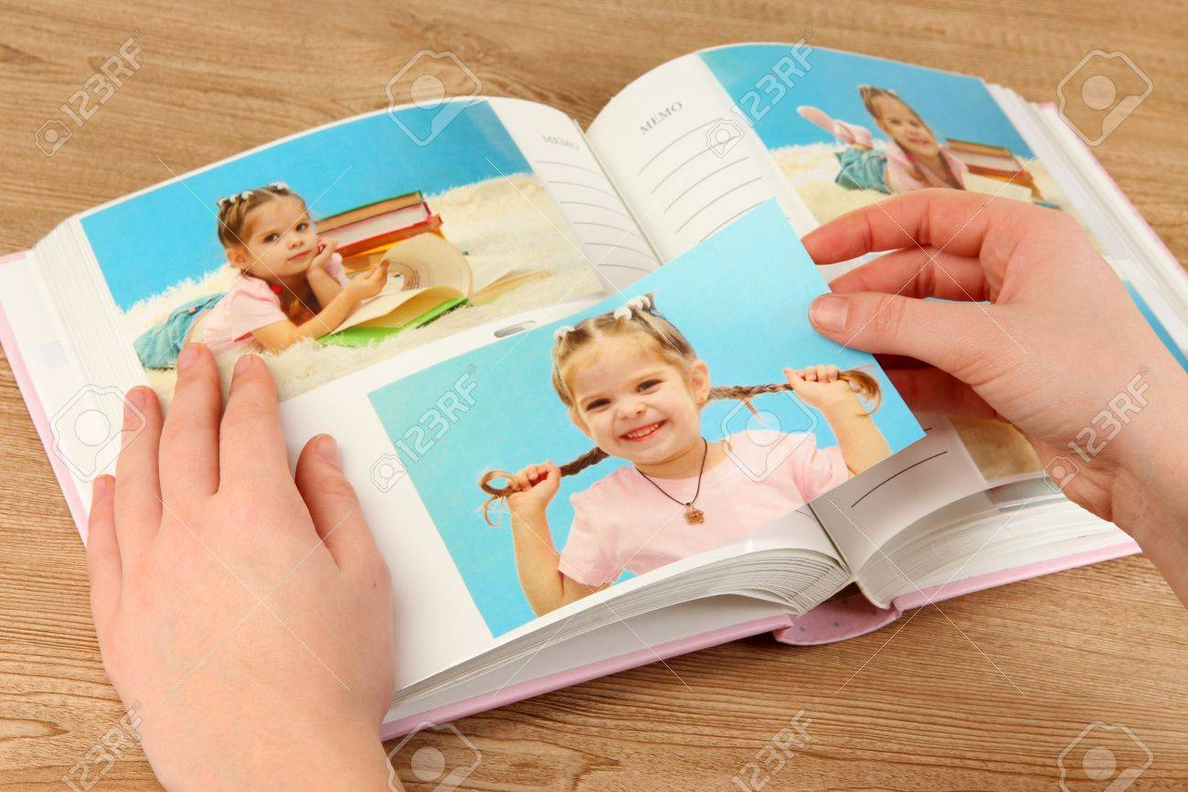 Photos in hands and photo album on wooden table Stock Photo - 19360675
