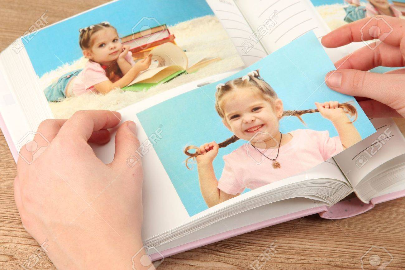 Photos in hands and photo album on wooden table Stock Photo - 19361147