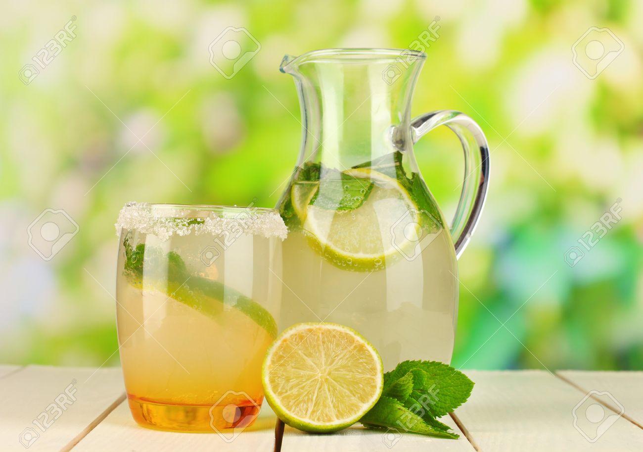citrus limonada en una jarra y vidrio sobre mesa de madera sobre fondo natural foto de