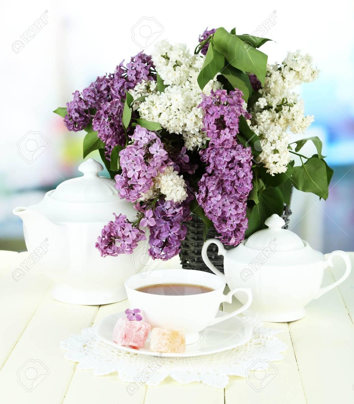 Foto de archivo , Composici?n con hermosas flores de color lila, servicio de t? en la mesa de madera sobre fondo brillante
