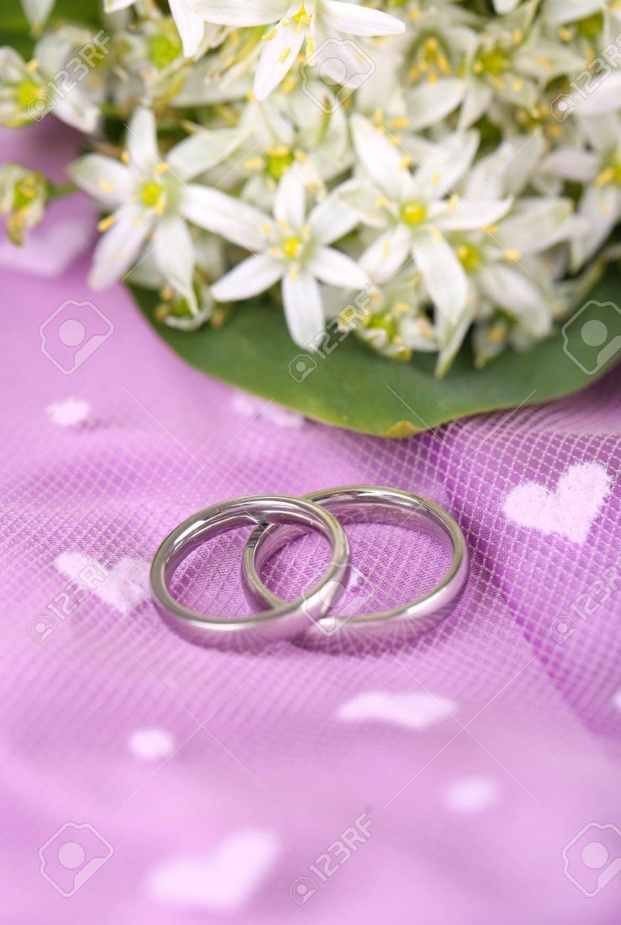 photo beautiful wedding rings on purple background purple wedding rings Beautiful wedding rings on purple background Stock Photo
