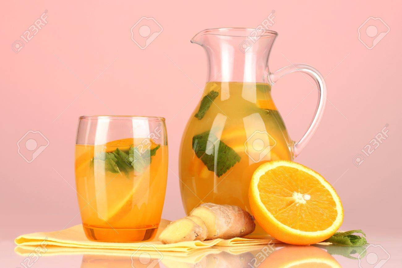 Orange lemonade in pitcher and glass on pink background Stock Photo - 20257828