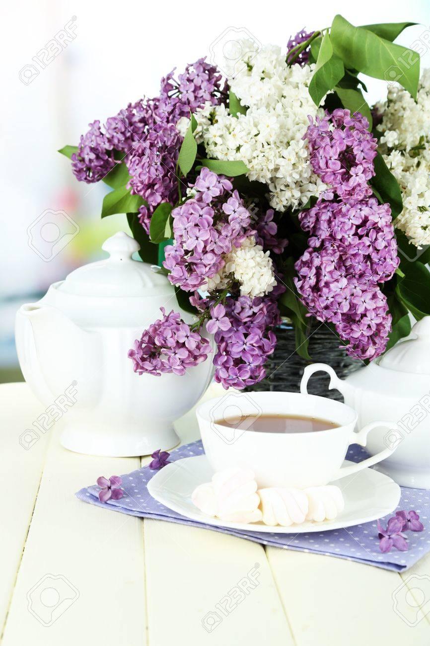 Foto de archivo , Composición con hermosas flores de color lila, servicio de té en la mesa de madera sobre fondo brillante