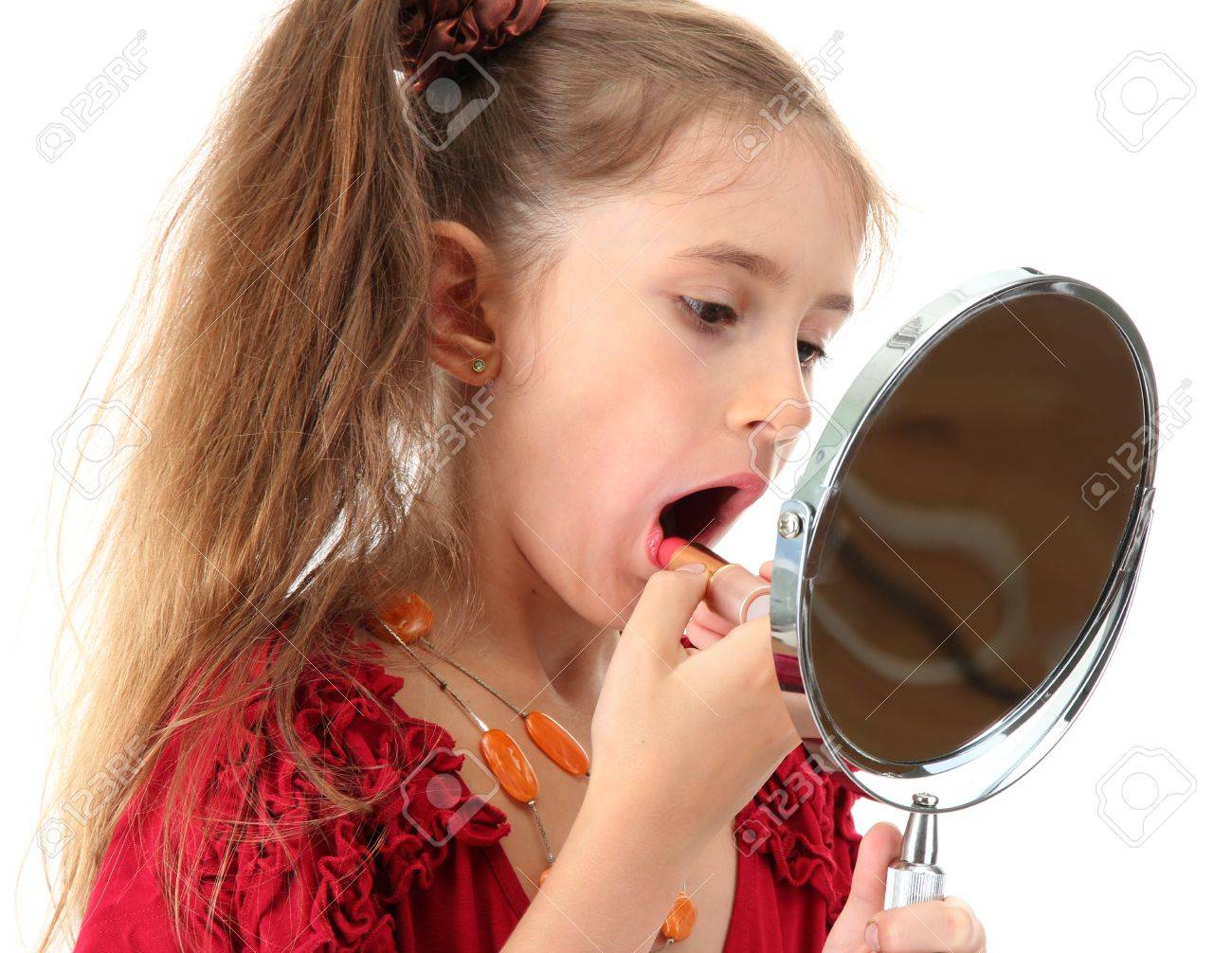 little girl in her mother's dress, is trying painting her lips, isolated on white Stock Photo - 21553371