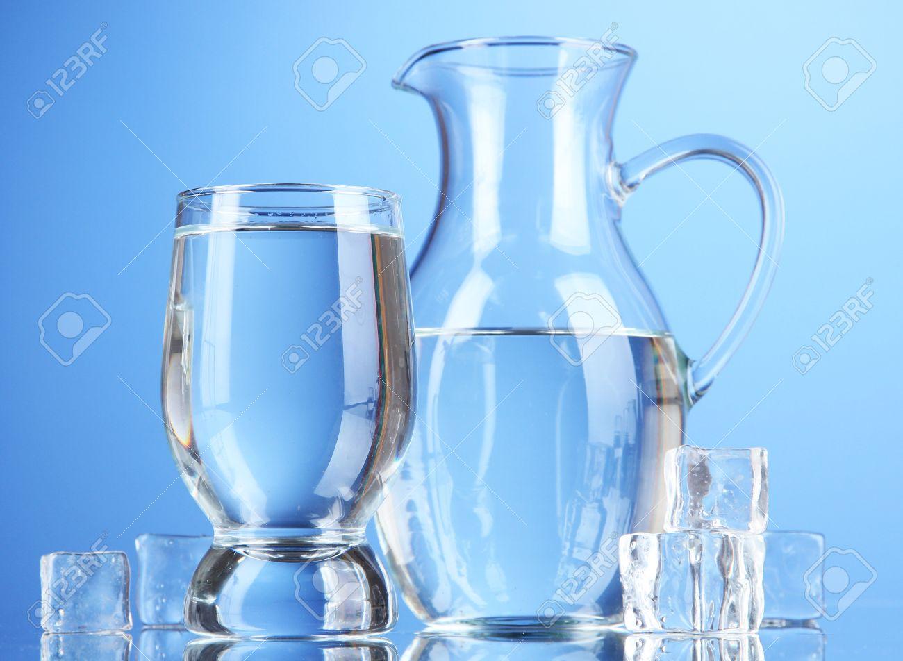 jarra de cristal de agua y el vidrio en el fondo azul foto de archivo
