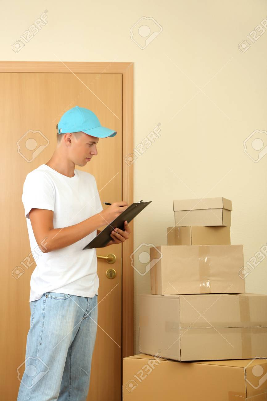 Young delivery man with parcels and clipboard, Stock Photo - 21554099