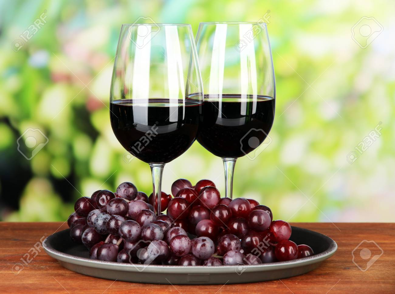 Ripe grapes and glasses of wine, on bright background Stock Photo - 21767865