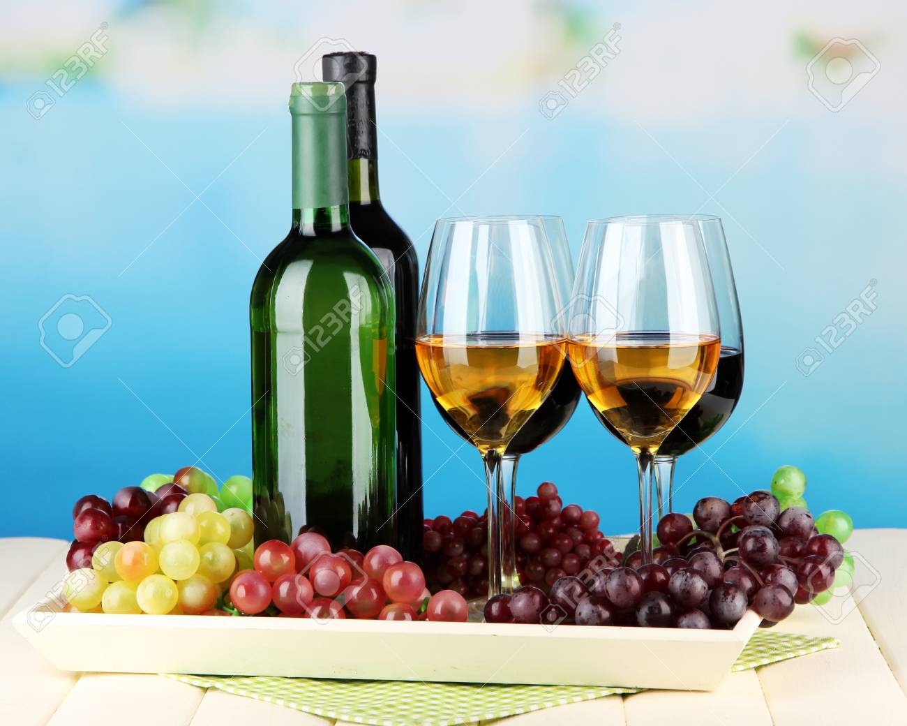 Wine bottles and glasses of wine on tray, on bright background Stock Photo - 21828695