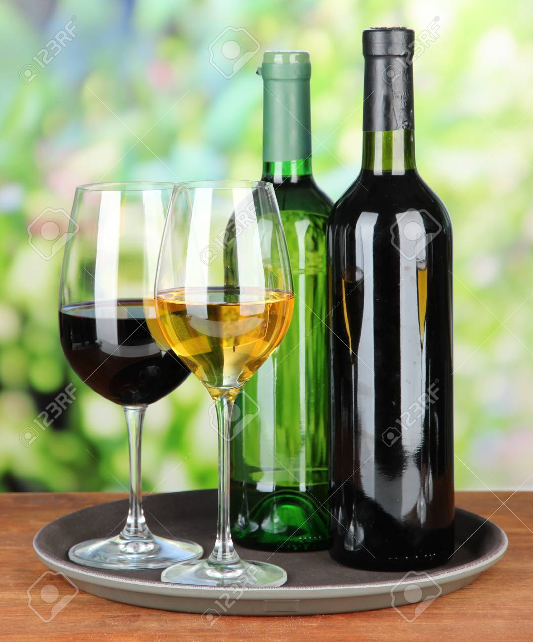 wine bottles and glasses of wine on tray on bright background stock