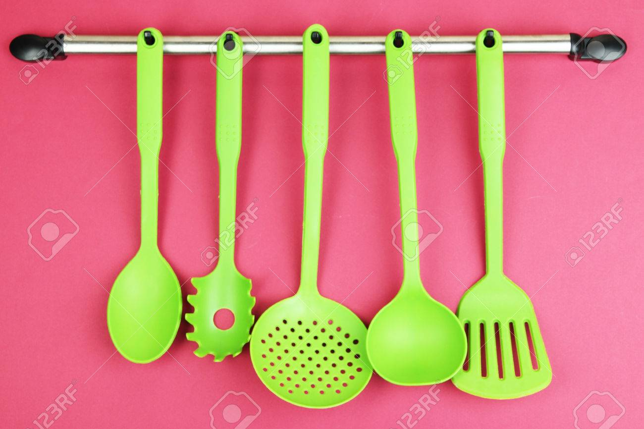Plastic Kitchen Utensils On Silver Hooks On Red Background Stock Photo    23801811