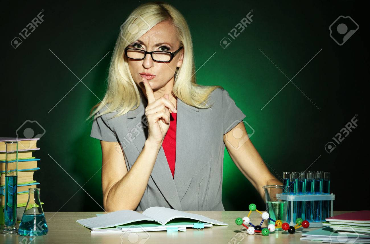 Wicked Chemistry Teacher Sitting At Table On Dark Colorful ...