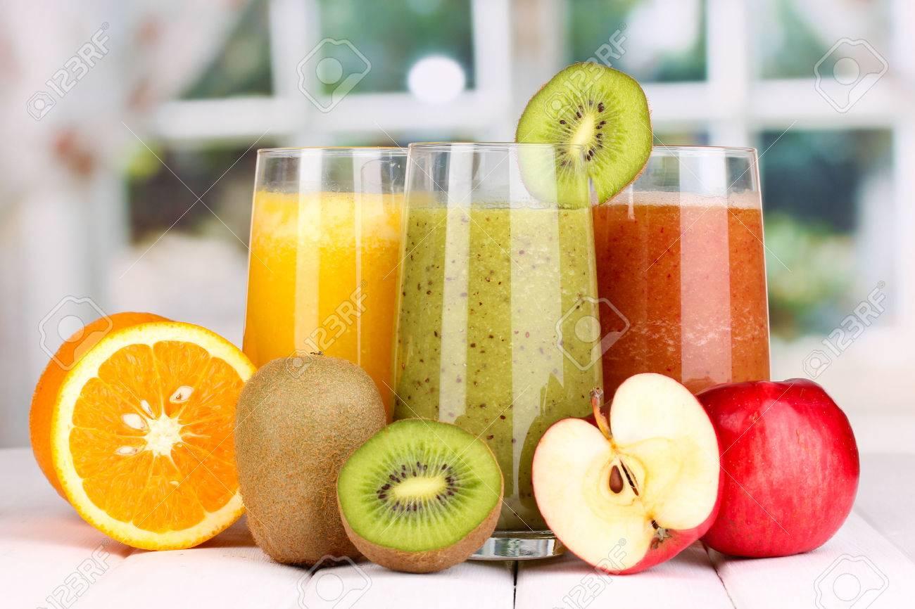 fresh fruit juices on wooden table on window background stock photo