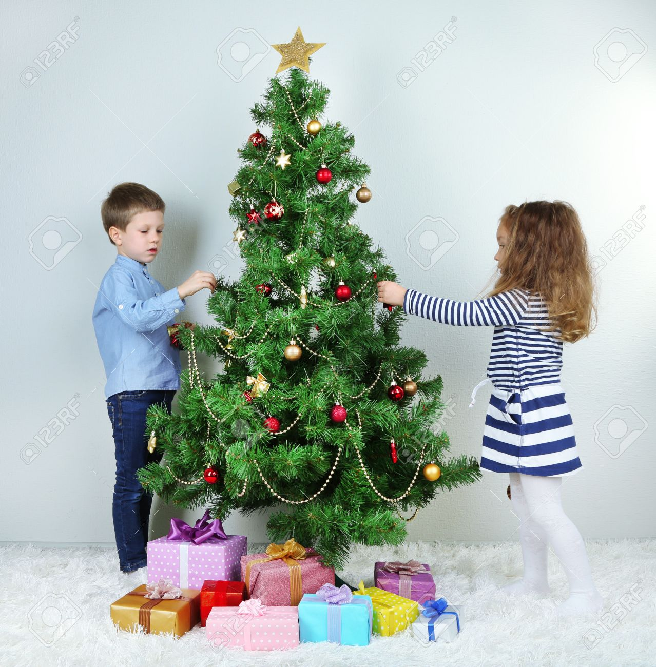 Kids Decorating For Christmas kids decorating christmas tree with baubles in room stock photo