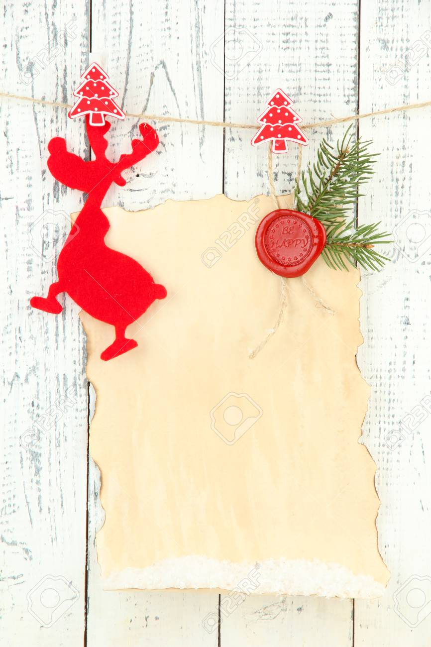 Blank Sheet With Christmas Decor Hanging On White Wooden Wall ...
