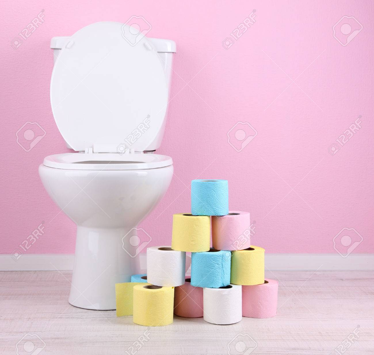 White toilet bowl and colorful rolls of toilet paper, in  bathroom Stock Photo - 25228874