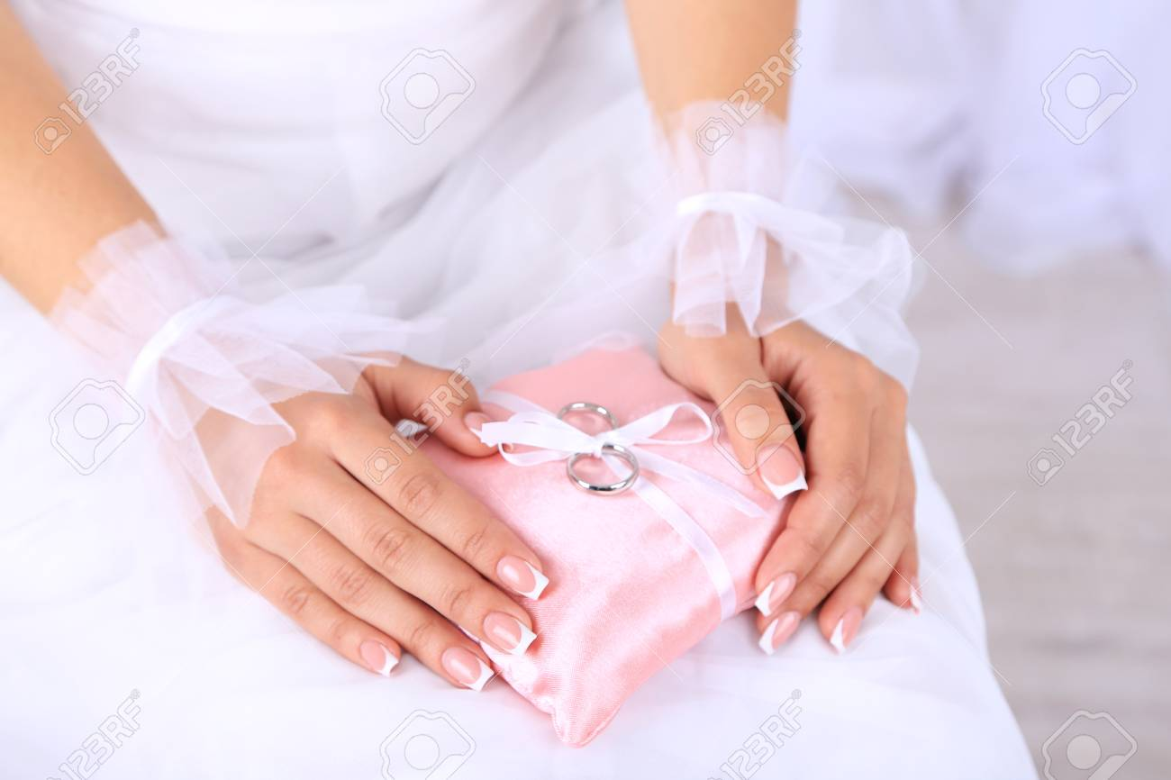 Bride In White Dress And Gloves Holding Decorative Pillow With ...