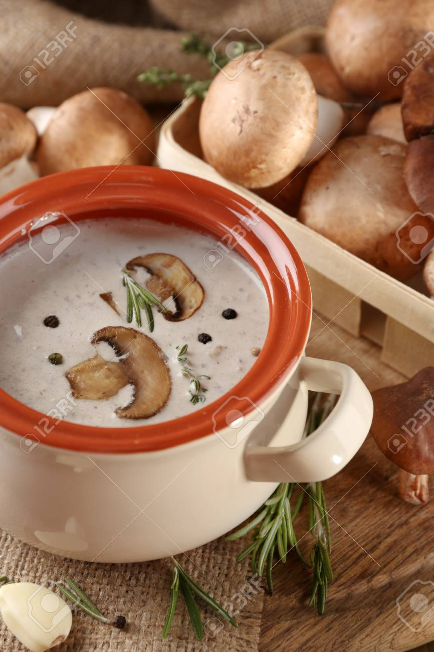 Composition with mushroom soup in pot, fresh and dried mushrooms, on wooden table, on sackcloth background Stock Photo - 28166509