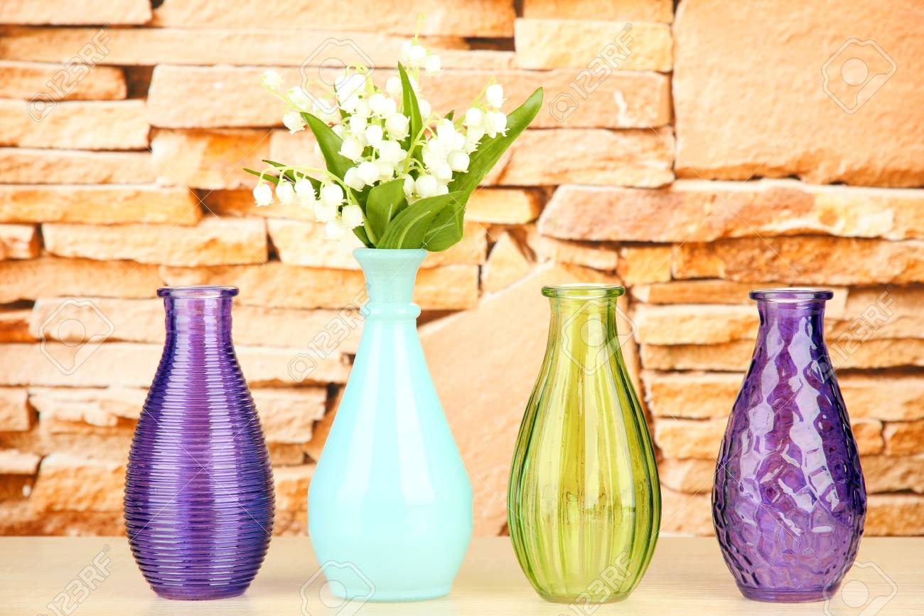 Different Decorative Vases On Shelf On Brick Wall Background Stock ...