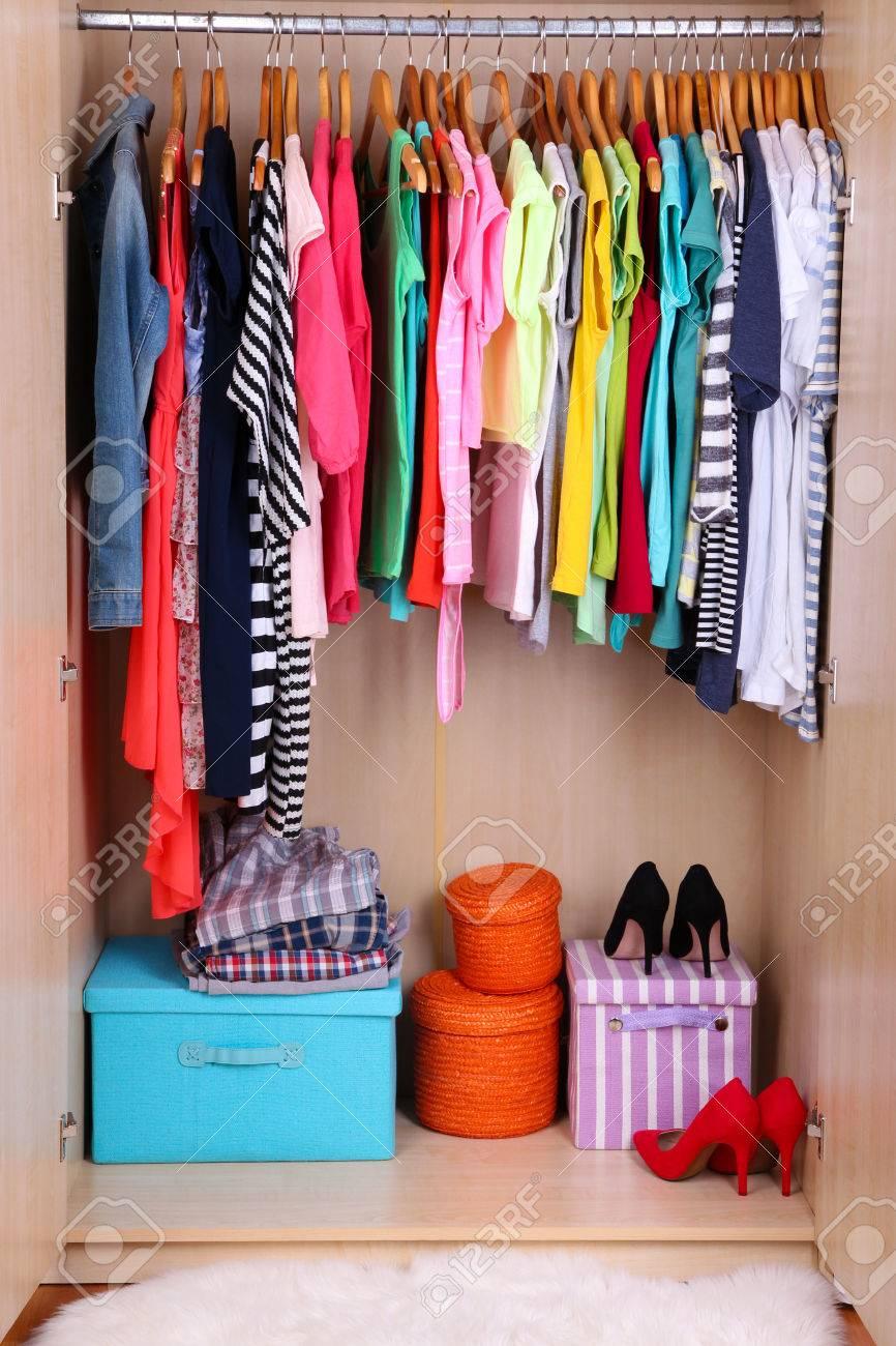ropa de colores colgando en el armario foto de archivo