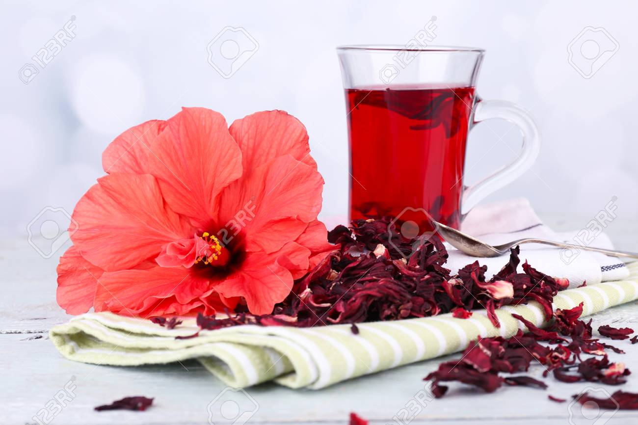 Hibiscus tea and flower on color napkin on wooden table, on light background - 32311131