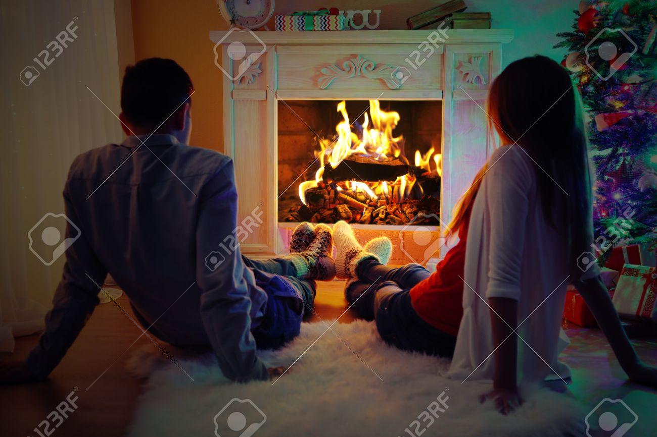 Bella coppia amore seduto sul tappeto davanti al camino. donna e ...