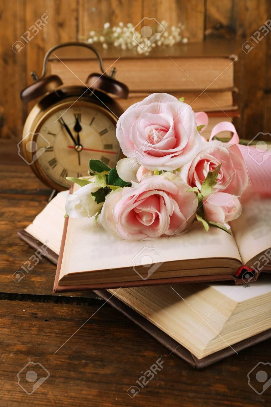 Bücher Mit Blumen Und Uhr Auf Holzuntergrund Lizenzfreie Fotos ...
