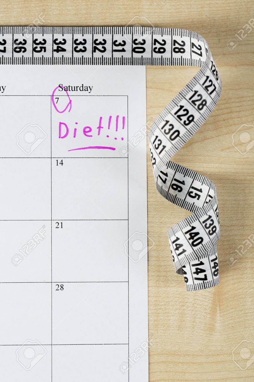 diet concept measure tape on calendar close up stock photo