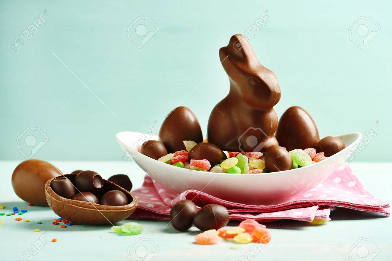 Chocolate Easter Eggs And Rabbit On Plate, On Color Wooden Background Stock  Photo   39420364